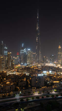 8/11/2020 - Dubai, United Arab Emirates: Iconic panorama at night of Burj Khalifa and Dubai Skyline with beautiful night colors on other skyscrapers in the Middle East (portrait view)