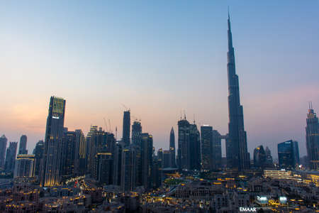 8/11/2020 - Dubai, United Arab Emirates: Iconic panorama at sunset of Burj Khalifa and Dubai Skyline as sun sets with and other skyscrapers in the Middle East with blue sky