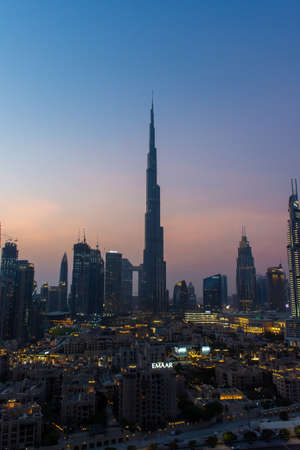 8/11/2020 - Dubai, United Arab Emirates: Iconic portrait at sunset of Burj Khalifa and Dubai Skyline as sun sets with and other skyscrapers in the Middle East with blue sky