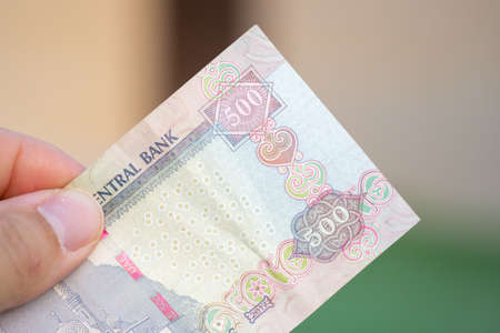 Hand holding Currency of the United Arab Emirates (UAE) - Close up of a purple five hundred Dirham note  on a blurred background. 免版税图像