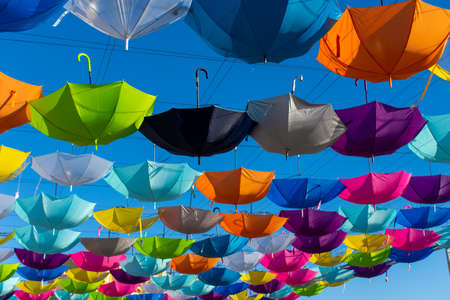 Colorful vibrant umbrellas hanging over the walking street for a festival on a blue sky sunny day (angle)
