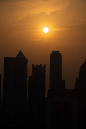 Dubai skyline at sunset with orange and yellow sky over the skyscrapers in the United Arab Emirates. (Portrait View)