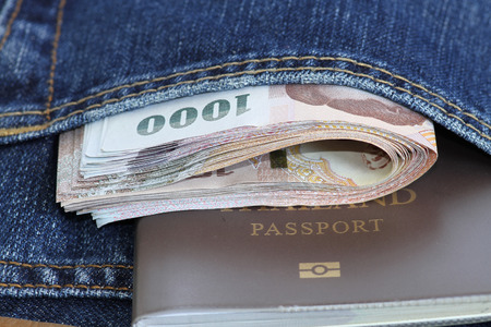jeans pocket: Thailand bank note and passport in jeans pocket. Stock Photo