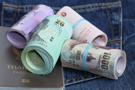 bank note: Roll of Thailand bank note and passport on jeans background