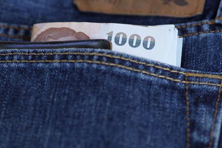 money pocket: Tailandia de billetes de banco y dinero de bolsillo en bolsillo de los vaqueros.