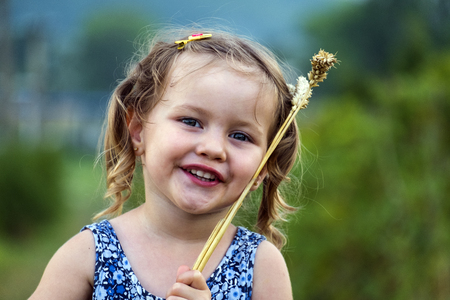 Little girl put wheat spikelets on the face