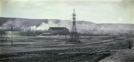 High-voltage line passing through the field in the background of the hills in the smoke. Black and white photo in retro style (Ukraine, Zolochiv)