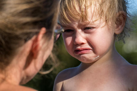 Little girl is crying bitterly. Mom scolds a little daughter who has been soiled in ice cream