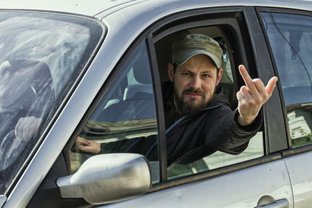 Sassy guy behind the wheel of a car stuck his hand out of the window and shows:  Fuck you! Imagens