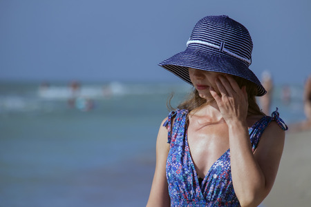 Young girl in a sundress stands on the beach and hides her eyes behind the brim of her hat 免版税图像