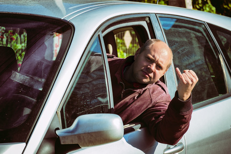 Impudent man at the wheel shows an indecent gesture with his little finger, thereby offering to go to bad places Stock Photo