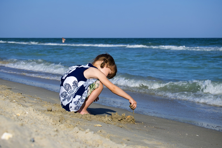 Little girl on the beach of the sea is building a sand castle Stock Photo