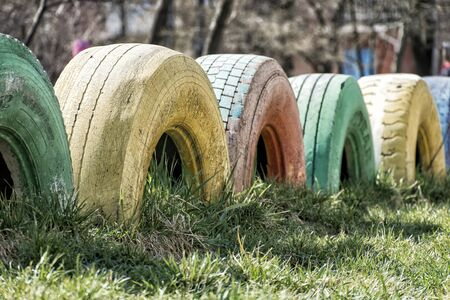 Vintage truck tires dug into the ground as fences and painted in different colors