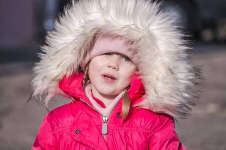 Little girl in a pink jacket and weathered lips in a good mood Stockfoto