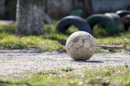 Old shabby leather soccer ball lying on the ground