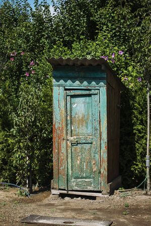 Rustic outdoor toilet stands in the garden sparkling, reflecting the sunshine light