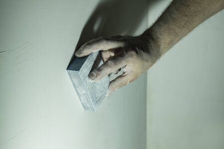Hand of the master grinds the wall with an abrasive sponge