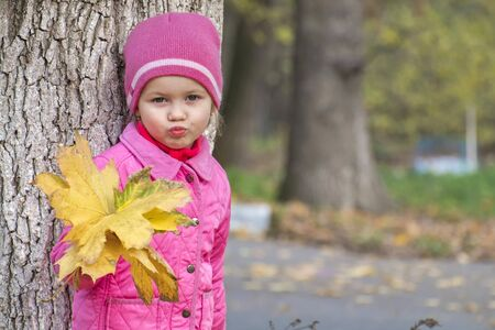 Little girl with a bouquet of autumn leaves folded her lips in the shape of a kiss Stockfoto