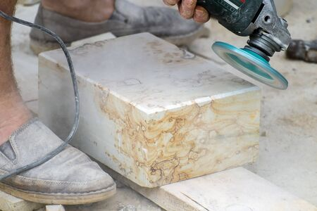 Angle grinder makes chamfer on antique travertine