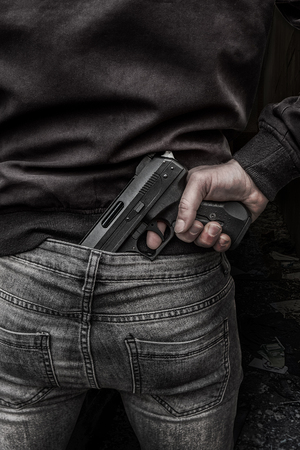 A man pulling his hand gun from the back of his jeans