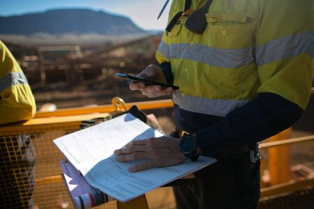Miner supervisor checking site emergency phone number before sigh of confined space permit prior to performing high risk work on construction mine site, Perth, Australia Archivio Fotografico
