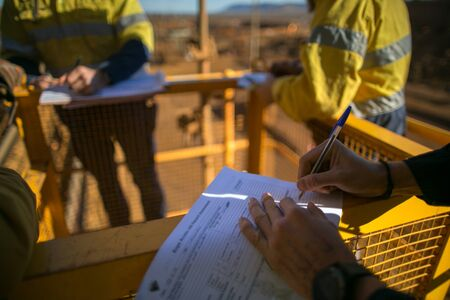 Rope access miner supervisor sigh of JSA risk assessment permit to work on site prior to performing high risk work on construction mine site, Perth, Australia Foto de archivo - 132853897