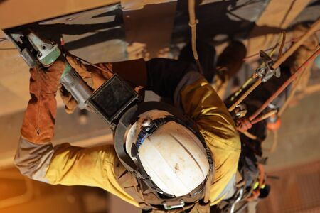 Tope view of rope access technician welder services working at height wearing safety glove hand protection, white helmet head fall protection PPE and using power grinder grinding metal wall prep Archivio Fotografico