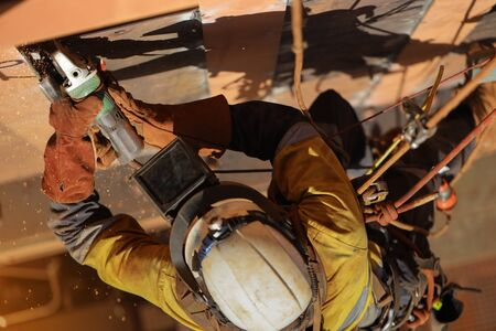 Tope view of rope access technician welder services wearing white helmet head fall protection PPE, face shield abseiling working at height using power grinder grinding wall preparation prior to weld