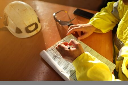Top view of young construction gold miner worker hand holding pen writing job hazards analysis on working at height risk assessment safety control permit prior to start morning shift during shut down Foto de archivo - 135132756