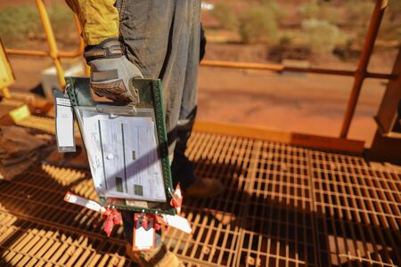 Senior miner supervisor dress as work uniform wearing a safety glove holding carry, safety control isolation lock box permit to work board on two weeks shut down operation construction mine site