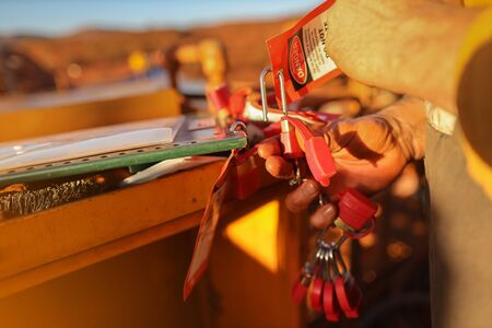 Close up male miner hand placing personal red danger lock which is attached together with danger tag into isolation safety control permit lock box at the opening field prior to starting each work