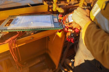 Close up miner hand placing personal red danger lock which is attached together with danger tag into isolation safety control permit lock box at the opening field prior to starting each work