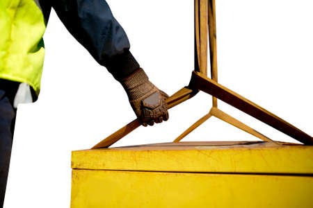 Trainesd rigger construction worker wearing heavy duty glove holding safety tag line on two tones yellow lifting sling which its connecting to the load while crane is lifting clipping path background