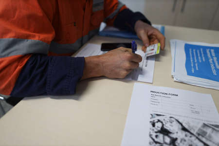 Safety workplace construction worker setting on a chair holding a pen signing of site safety induction rule and regulation evacuation plan prior first time working on site