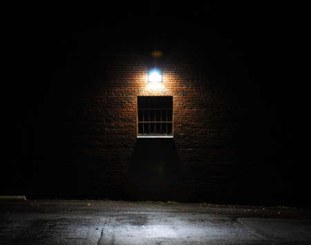 Dark single window in a brick wall lit from above by a bright light at night Stock Photo - 17178365