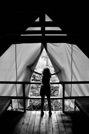 Girl silhoutted and framed by curtains while looking outside into forest Stock Photo