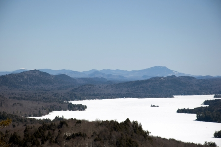 Scenic landscape view of frozen mountain lake in Adirondack Mountains of New York State during a clear sunny spring day  Stock Photo