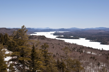 Scenic alpine view of lake and mountains in Adirondack Mountains of New York State during a clear sunny spring day