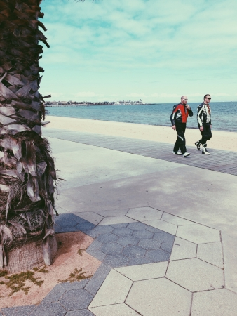st kilda: Two with cycle jersey walking at St Kilda beach side