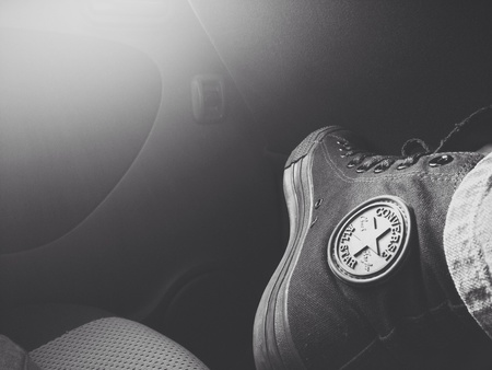 converse: Black converse shoe with sun flare  Stock Photo