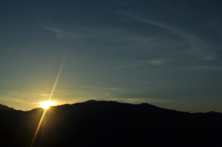 Sunrise flare with mountain silhouette photo
