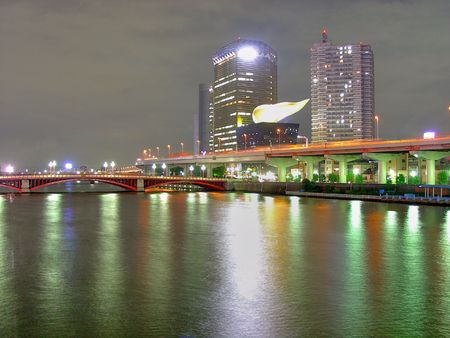 lupulus: Sumidagawa River at night in Asakusa district in Tokyo, Japan. The thing over the building is supposed to be beer lupulus, and is a popular spot for people living there. Stock Photo