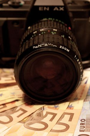 microstock: Reflex camera lenses over 20 and 50 Euro notes, showing working for microstock sites pays when you do your best to create quality shots.