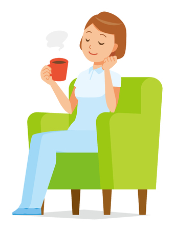 A woman nurse in a white uniform sits on a sofa and is drinking coffee.