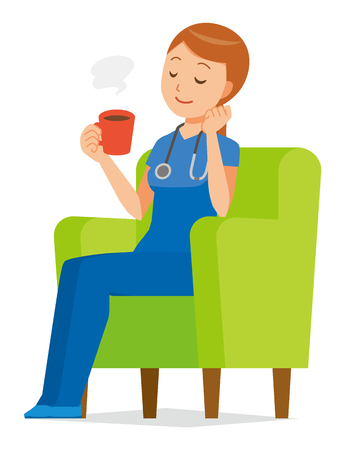 A woman nurse in a blue scrub is sitting on a sofa and drinking coffee.