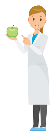 A female doctor wearing a white coat has a green apple