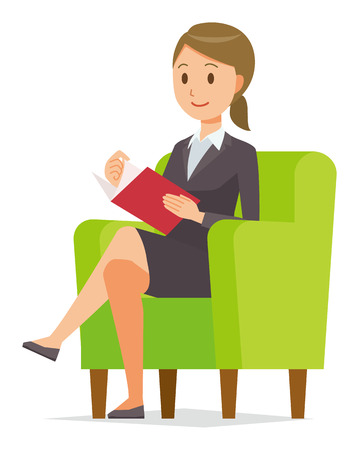A business woman in a suit sits on a sofa and is reading books.