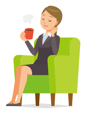 A business woman in a suit sits on a sofa and is drinking coffee.