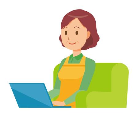 Una ama de casa de mediana edad con un delantal está sentada en un sofá y opera una computadora portátil