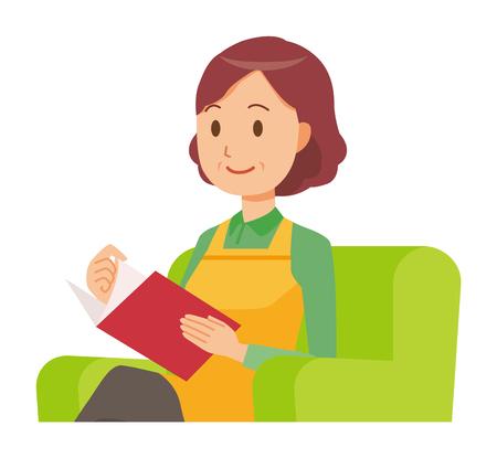 Eine Hausfrau mittleren Alters mit einer Schürze liest auf einem Sofa